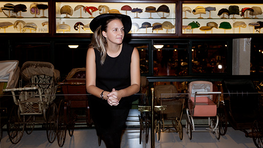 Yasemin Genç Uygur in front of her Hat Collection